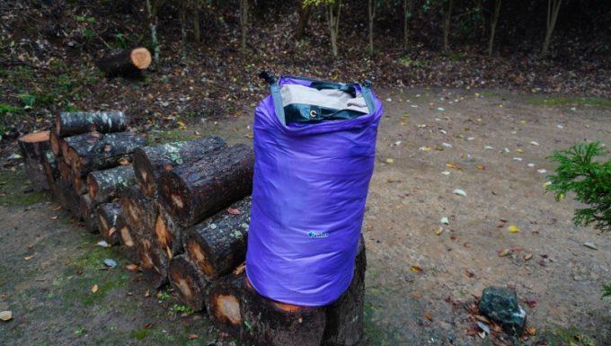 雨撤収で泥に汚れて濡れたテントが入ったドライバック