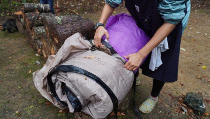 雨撤収で泥に汚れて濡れたテントをドライバックに入れる