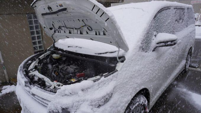 雪の降る中で車のボンネットを開けた写真