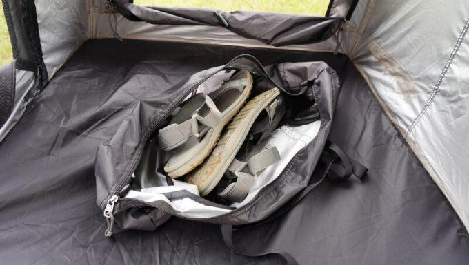 KAZUMI ブラックコットテントの収納袋に靴をしまう